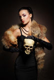 Young woman in luxurious fur posing with a skull Stock Photography