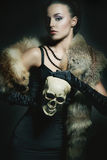 Young woman in luxurious fur posing with a skull Royalty Free Stock Photos