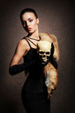 Young woman in luxurious fur posing with a skull. Young, rich and beautiful woman with the scull over the vintage background. Halloween concept royalty free stock image