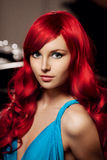 Young woman with luxurious long beautiful red hair in a blue fas Stock Photography