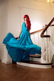 Young woman with luxurious long beautiful red hair in a blue fas Royalty Free Stock Photo