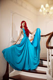 Young woman with luxurious long beautiful red hair in a blue fas Stock Photos