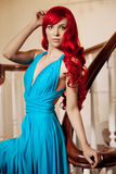Young woman with luxurious long beautiful red hair in a blue fas Stock Photo