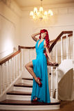 Young woman with luxurious long beautiful red hair in a blue fas Royalty Free Stock Photos