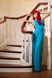 Young woman with luxurious long beautiful red hair in a blue fas Stock Image