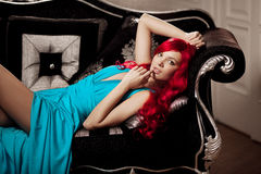 Young woman with luxurious long beautiful red hair in a blue fas Royalty Free Stock Photography