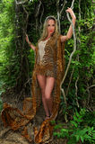 Young woman in luxury animal print dress among the jungle Stock Photo