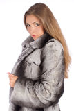 Young woman in luxury fur coat looking at camera. Isolated on white background Royalty Free Stock Images