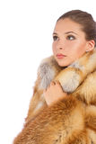 Young woman in luxury fur coat looking at the left. Isolated on white background Stock Image