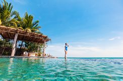Young woman at luxury resort. Young beautiful woman walking along infinity pool at tropical resort Stock Photo