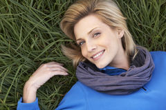 Young woman lying alone on grass Stock Photo