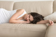 Young woman lying asleep on couch, taking nap at home Royalty Free Stock Image