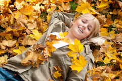 Young woman lying in autumn leaves. Beautiful young blond woman lying in autumn leaves stock image
