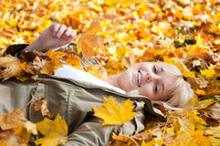 Young woman lying in autumn leaves. Beautiful young blond woman lying in autumn leaves stock images