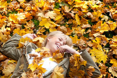 Young woman lying in autumn leaves. Beautiful young blond woman lying in autumn leaves stock photo