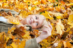 Young woman lying in autumn leaves. Beautiful young blond woman lying in autumn leaves royalty free stock photography