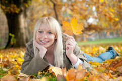 Young woman lying in autumn leaves. Beautiful young blond woman lying in autumn leaves royalty free stock images