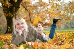 Young woman lying in autumn leaves. Beautiful young blond woman lying in autumn leaves royalty free stock photos