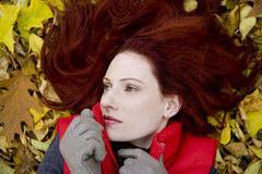 A young woman lying on autumn leaves Royalty Free Stock Photo