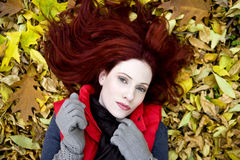 A young woman lying on autumn leaves Royalty Free Stock Photos