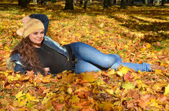 Young woman lying in autumn leaves and smiling Stock Image