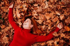 Young woman lying on the autumn leaves. In the park stock photo