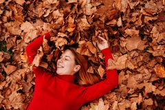 Young woman lying on the autumn leaves. In the park royalty free stock images
