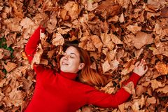 Young woman lying on the autumn leaves. In the park stock image