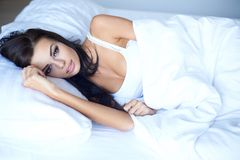 Young woman lying awake in bed thinking Royalty Free Stock Photography