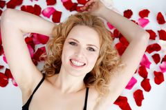 Young woman lying back in rose petals on hood of N Royalty Free Stock Photos