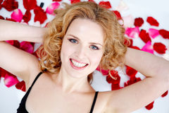 Young woman lying back in rose petals on hood of N Stock Images