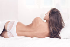 Young woman lying with a bare back. Beautiful and sexy young woman, lying with a bare back Stock Image