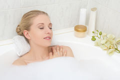 Young woman lying in bath with foam and orchid flower Royalty Free Stock Photo