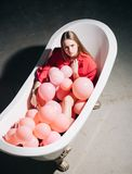 Young woman lying in a bathtub full of foam of pink bubbles colorful balloons. Stock Images