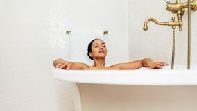 Young woman lying in bathtub with her eyes closed. At home royalty free stock photography