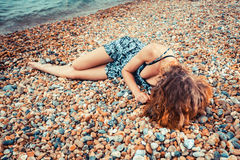 Young woman lying on the beach Stock Images