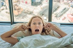 Young woman lying on a bed covered her ears because of the noise. In the window after the bed you can see the construction of a new house stock photography