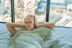 Young woman lying on a bed covered her ears because of the noise. In the window after the bed you can see the royalty free stock photography