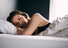 Young woman lying in bed daydreaming Royalty Free Stock Photos