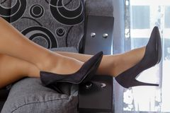 Beautiful women`s legs with black shoes on the bed stock photo