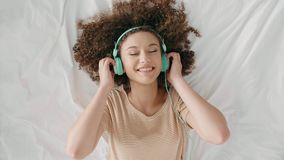 Young woman lying on the bed and listening to music. In her bedroom stock footage
