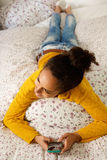 Young woman lying on bed with mobile phone Royalty Free Stock Photos