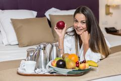 Young woman lying on bed near plate of fruits stock photos