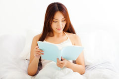 young Woman lying in bed while reading a book Stock Photo
