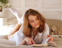 Young woman lying in bed while reading a book Royalty Free Stock Photos