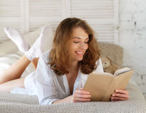 Young woman lying in bed while reading a book Royalty Free Stock Image