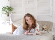 Young woman lying in bed while reading a book Royalty Free Stock Photography