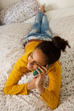 Young woman lying in bed and talking on cell phone Royalty Free Stock Images