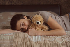 Young woman lying on the bed with a teddy bear Royalty Free Stock Photography
