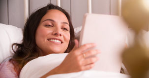 Young Woman Lying In Bed Using Digital Tablet Stock Images